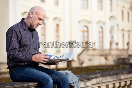 adult senior men outdoor sitting reading