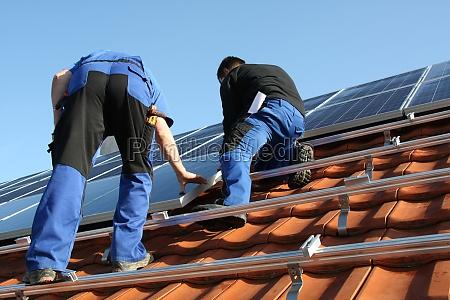 workmen are mounting solar paneels