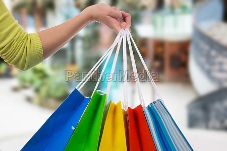 eine junge frau haelt einkaufstaschen in