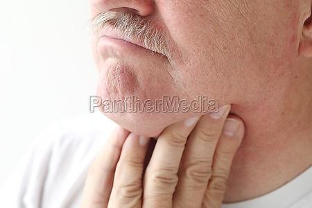 nahaufnahme des mannes mit halsschmerzen