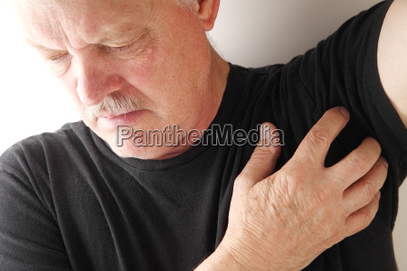 senior man scratches under his arm