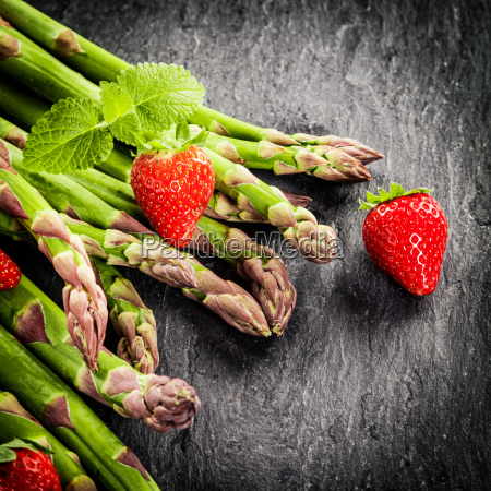 frische gruene spargelstangen und erdbeeren