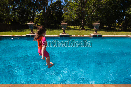 girl jumping swimming pool summer