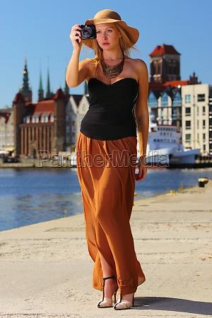 stylish traveler woman with camera gdansk