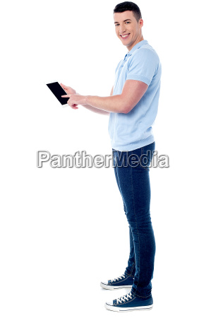 smiling guy operating his tablet pc