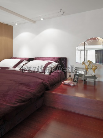 red bed and hardwood floor in
