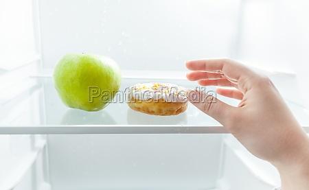 handwahl zwischen apfel und donut im