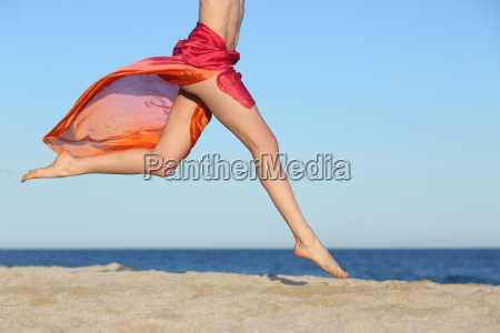 woman legs jumping on the beach