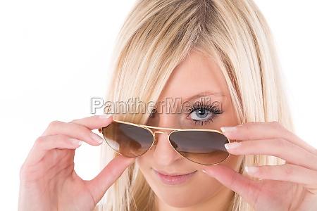 woman looks over edge of sunglasses