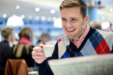 smiling man reading newspaper at restaurant