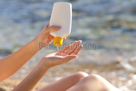 woman hands putting sunscreen from a