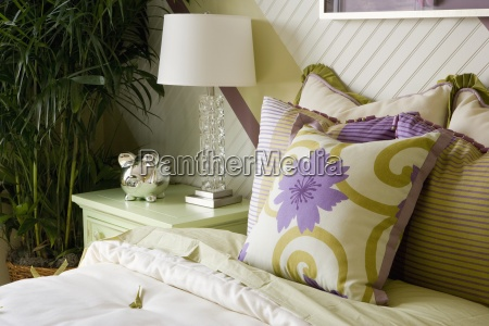 green and purple pillows on bed