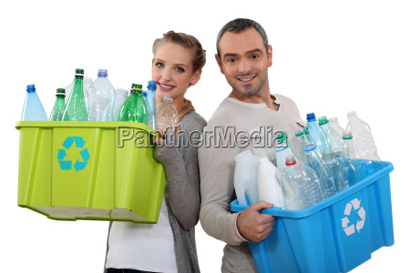 couple recycling empty plastic bottles