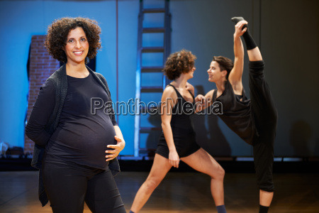pregnant woman teaching dance to students