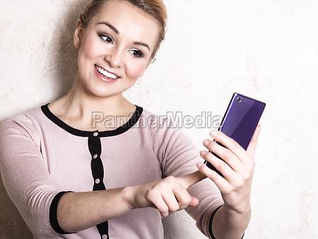 geschaeftsfrau liest sms auf einem smartphone