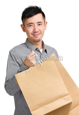 junger mann mit einkaufstasche
