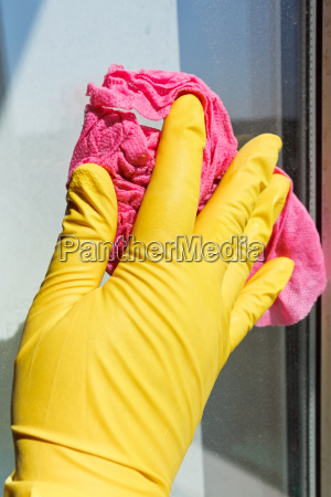 hand in gelb handschuh waschen fensterglas