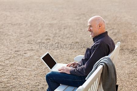 geschaeftsmann senior mit notebook laptop