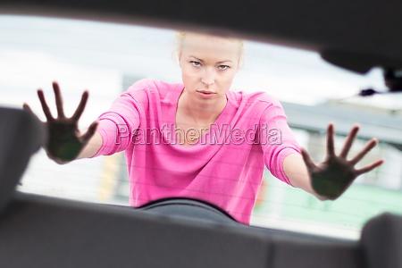woman pushing a car