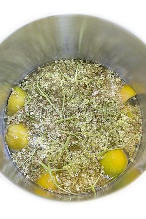 holunderblueten mit zitronen in wasser eingelegt