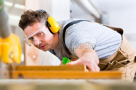carpenter mit elektrischen saege in einer