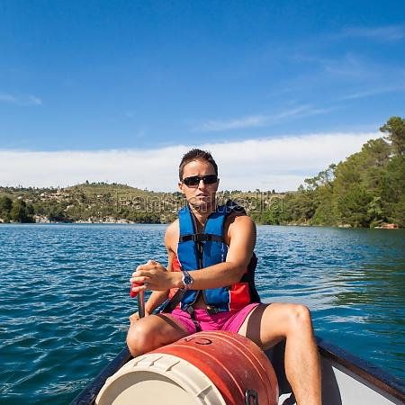 huebscher junger mann auf dem kanu