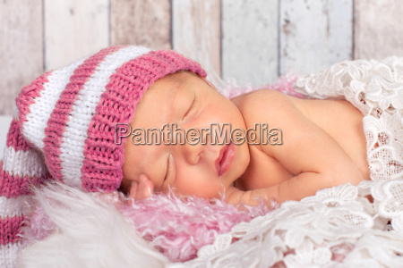 kleines baby mit rosa muetze