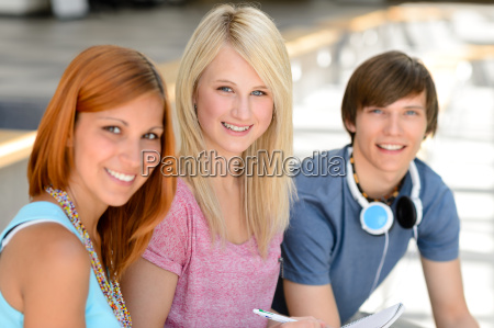 three smiling student friends looking at