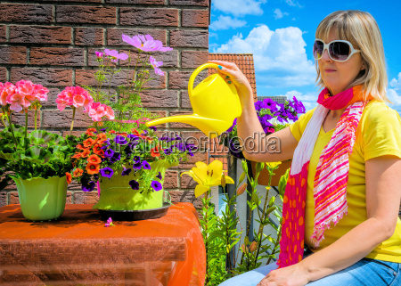woman pours flowers on the balcony