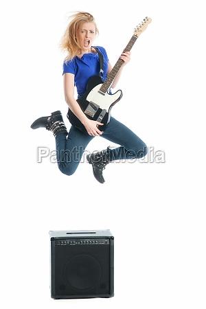 blondes maedchen spielt gitarre und springt