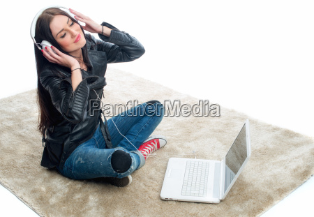 young woman with laptop and headphones