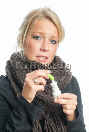 a cold woman with nasal spray