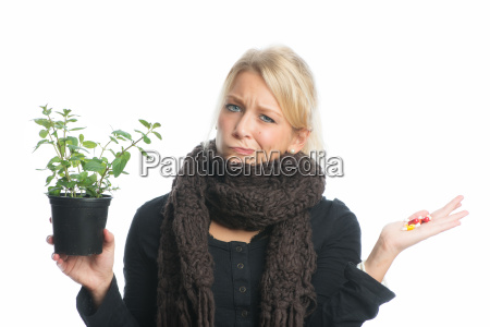 woman with medicinal plant and capsules