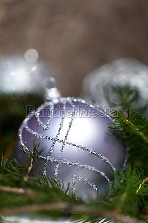 silberne christbaumkugeln in gruenen tannenzweigen mit