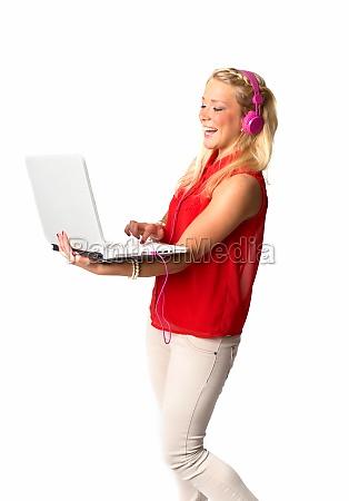 frau mit kopfhoerer und laptop