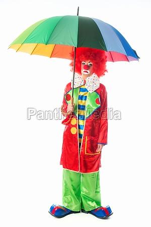 sad clown with umbrella