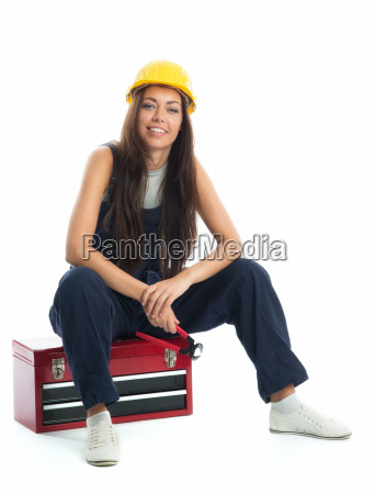 female apprentice sitting on toolbox