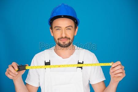 laechelnde workman haelt eine bandmessung