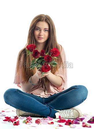 girl sits amid rose petals