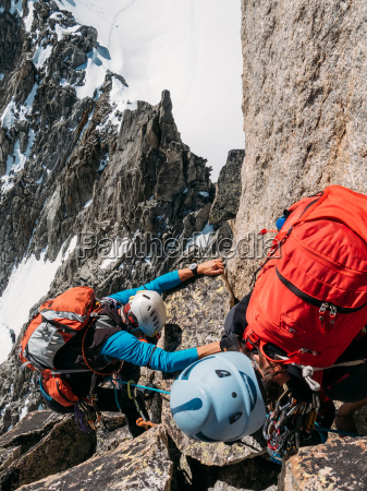 young female climber helps another climber