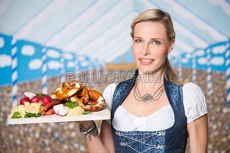 frau mit bayrischen spezialitaeten