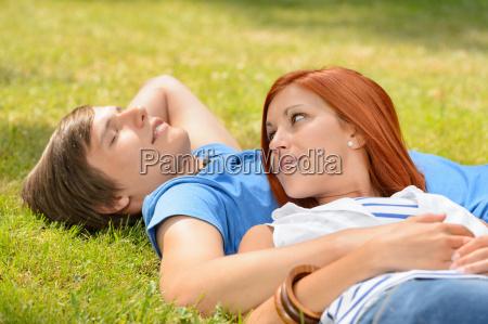 romantic teenage couple lying on grass
