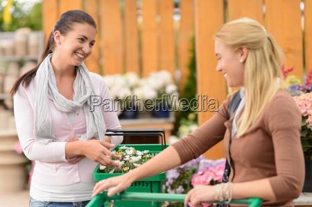 two smiling woman shopping plants garden