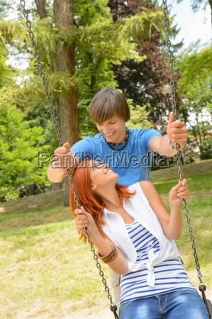 teenage couple girl sitting on swing