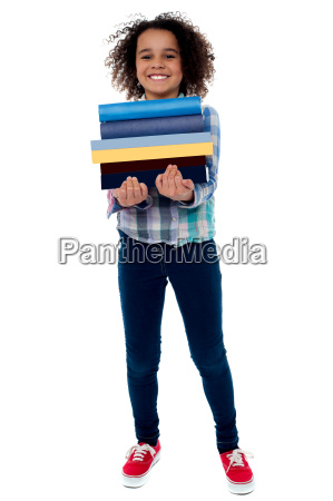 cute little girl carrying stack of