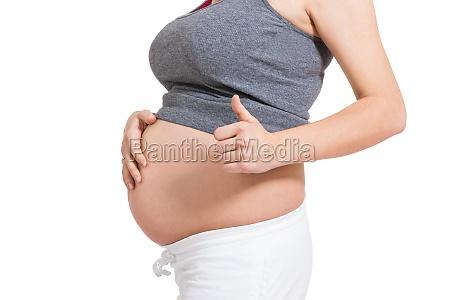 junge frau mit babybauch in erwartungsvoller