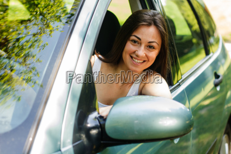 glueckliche junge frau die ein auto