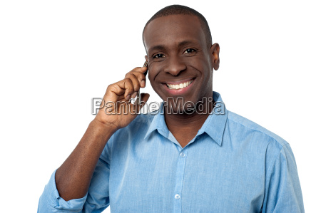 happy african guy attending a phone