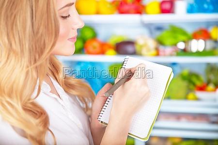 nette hausfrau schreibt liste an supermarkt
