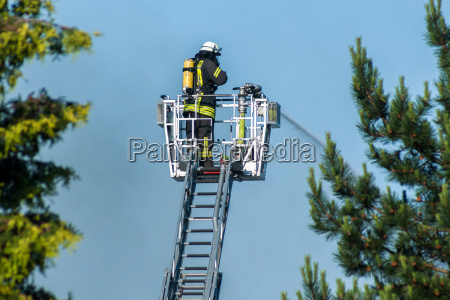 firefighter extinguishing fire from the large